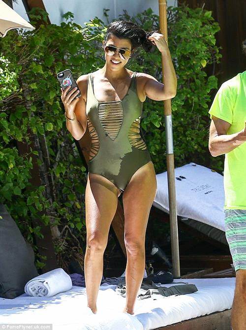 Kourtney Kardashian stretches at the poolside, giving an extra view of her tanned shoulder.