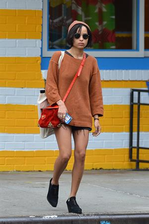 Zoe Kravitz walking in shorts and an orange top