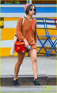 Zoe Kravitz walking in shorts and an orange top
