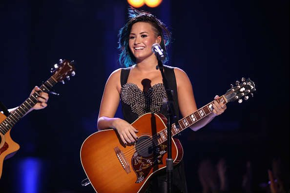 Demi plays guitar