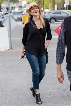 Julie Benz walking in jeans and a hat