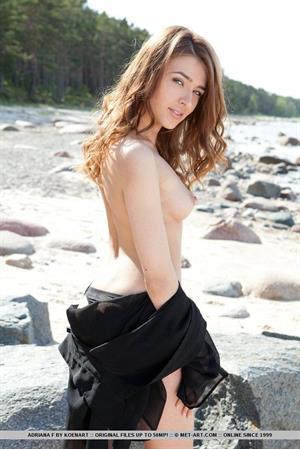 Adriana F poses on a rocky shore