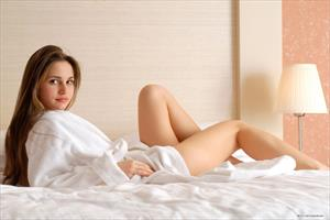 Anya posing on a bed