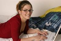 Sara Sexton on the bed with her laptop